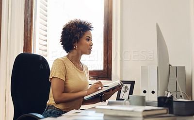 Buy stock photo Shot of a young businesswoman working on a computer while going through notes from a book in an office