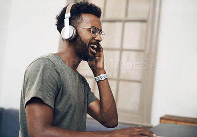 Buy stock photo Shot of a young businessman using headphones while working in a modern office