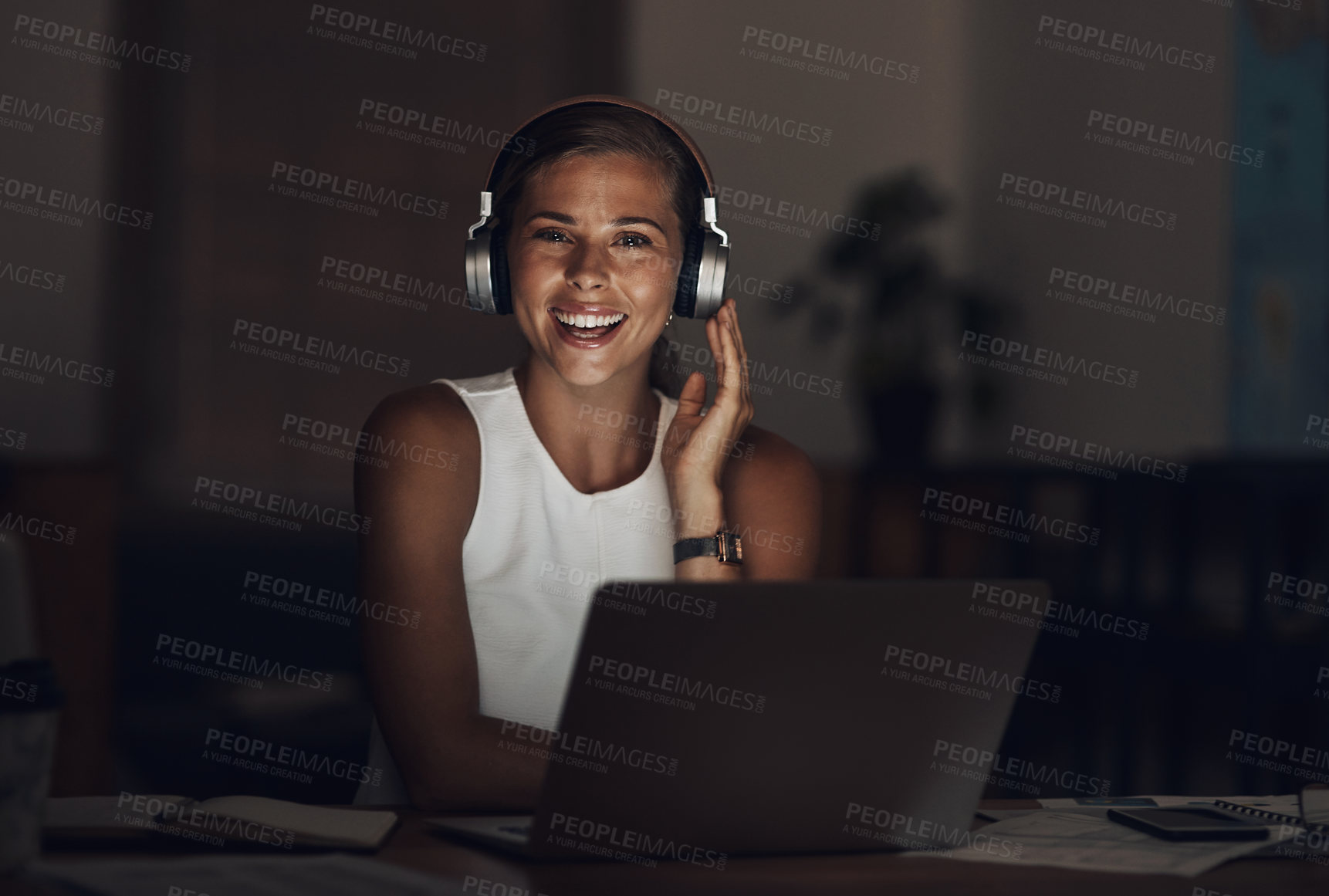 Buy stock photo Shot of a young businesswoman using headphones and a laptop during a late night in a modern office