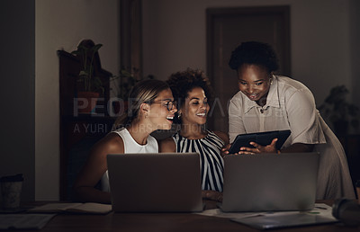 Buy stock photo Shot of a group of young businesswomen using a laptop and digital tablet during a late night at work
