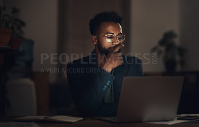 Buy stock photo Shot of a young businessman using a laptop during a late night at work