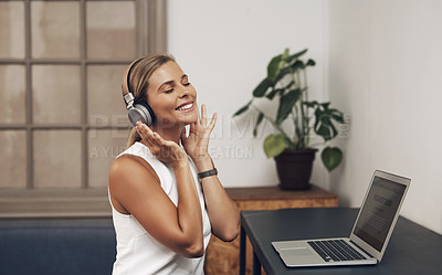 Buy stock photo Shot of a young businesswoman using headphones and a laptop in a modern office