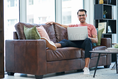 Buy stock photo Shot of a young man using a laptop while relaxing on a sofa