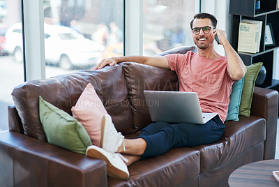 Buy stock photo Shot of a young man using a laptop and smartphone while relaxing on a sofa
