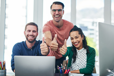 Buy stock photo Portrait of a group of young businesspeople showing thumbs up while using a computer in a modern office