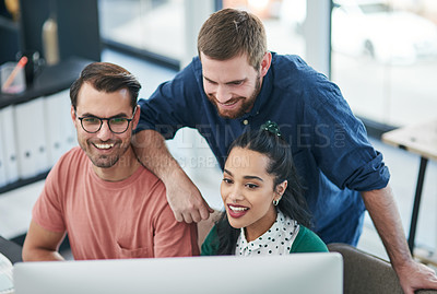 Buy stock photo Shot of a group of young businesspeople using a computer together in a modern office