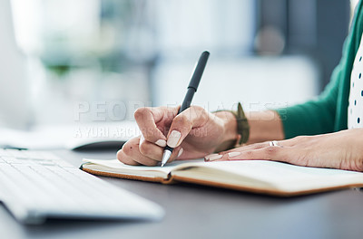 Buy stock photo Cropped shot of a businesswoman writing in a notebook at her desk in a modern office