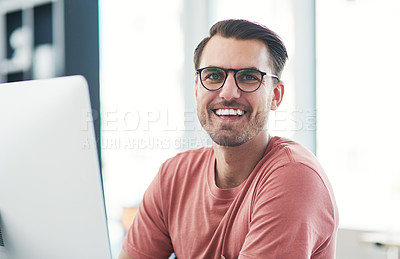 Buy stock photo Portrait of a young businessman using a computer in a modern office