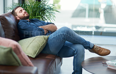 Buy stock photo Shot of a young man relaxing on a sofa