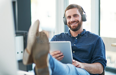 Buy stock photo Shot of a young businessman using a digital tablet and headphones in a modern office