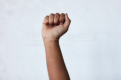 Buy stock photo Shot of an unrecognisable woman raising her hand in strength against a studio background