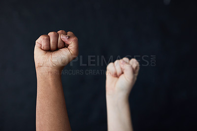 Buy stock photo Studio shot of two women raising their hands in solidarity against a dark background