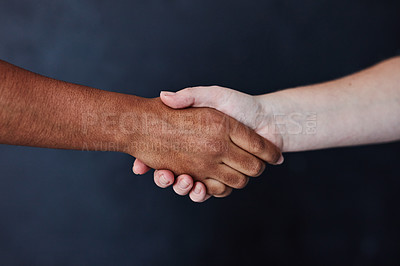 Buy stock photo Studio shot of two unrecognisable women shaking hands against a dark background