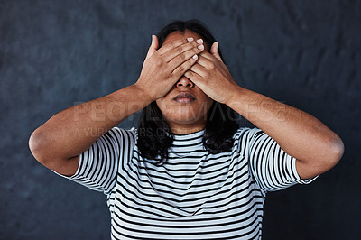 Buy stock photo Studio shot of a young woman covering her eyes against a dark background