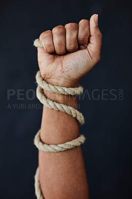 Buy stock photo Studio shot of an unrecognisable woman bound with rope and raising her hand in strength against a dark background