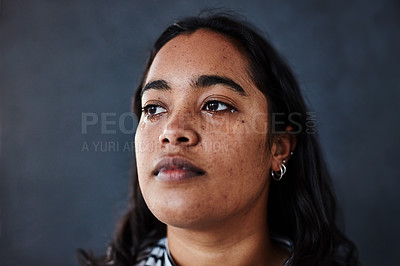 Buy stock photo Studio shot of a young woman crying against a dark background