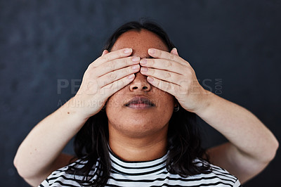 Buy stock photo Studio shot of a young woman with her attacker's hand covering her eyes against a dark background