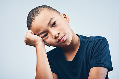 Buy stock photo Studio shot of a cute little boy looking bored against a grey background