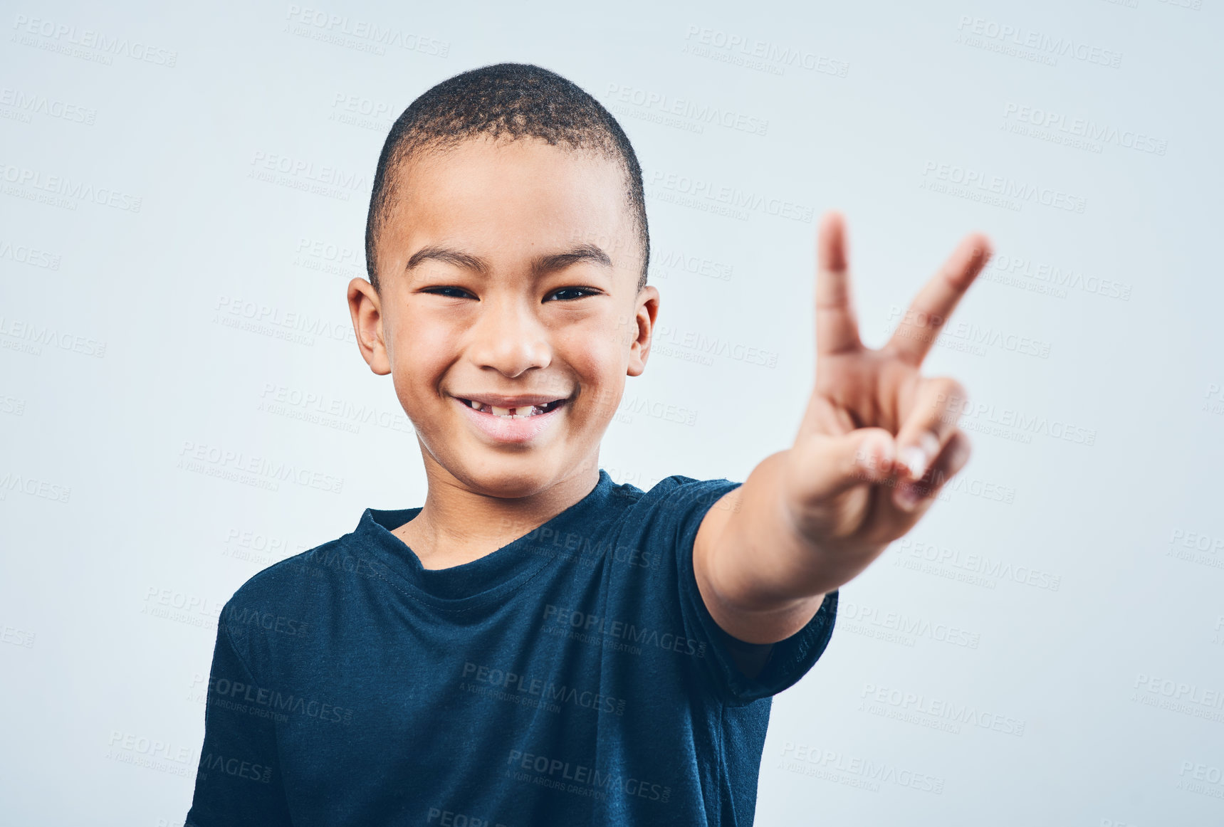 Buy stock photo Studio shot of a cute little boy making a peace sign against a grey background