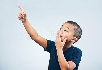Buy stock photo Studio shot of a cute little boy pointing and looking amazed against a grey background