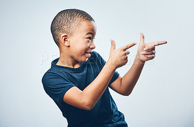 Buy stock photo Studio shot of a cute little boy pointing against a grey background