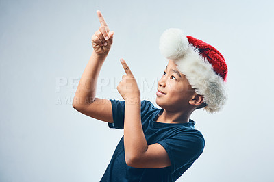 Buy stock photo Studio shot of a cute little boy wearing a Santa Claus hat and pointing against a grey background
