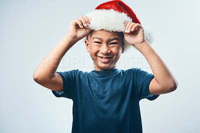 Buy stock photo Studio shot of a cute little boy wearing a Santa hat against a grey background