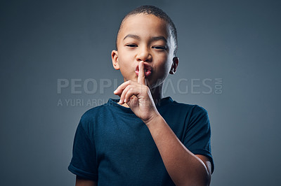 Buy stock photo Studio shot of a cute little boy posing with his finger on his lips against a grey background
