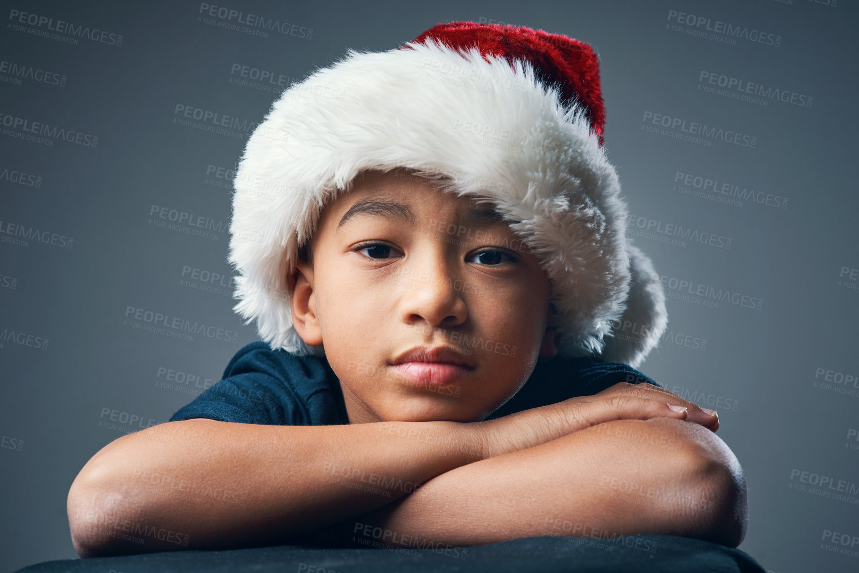 Buy stock photo Studio shot of a cute little boy wearing a Santa hat and looking serious against a grey background