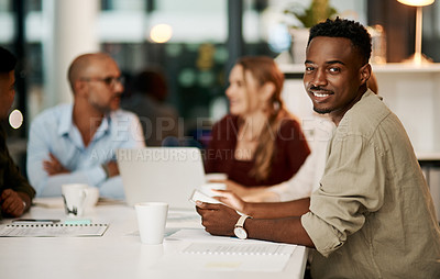 Buy stock photo Portrait of a young businessman using a digital tablet during a team meeting in a modern office