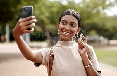 Buy stock photo Shot of a young businesswoman taking selfies with a smartphone and holding a tube of lipgloss  against a city background