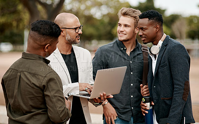 Buy stock photo Shot of a group of businessmen using a laptop against a city background