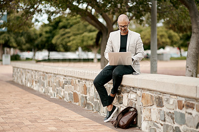Buy stock photo Shot of a mature businessman sitting on a wall and using a laptop against a city background