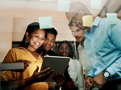 Buy stock photo Shot of a group of businesspeople using a digital tablet during a late night brainstorming session in a modern office