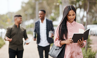 Buy stock photo Shot of a young businesswoman going through her notebook while walking through the city