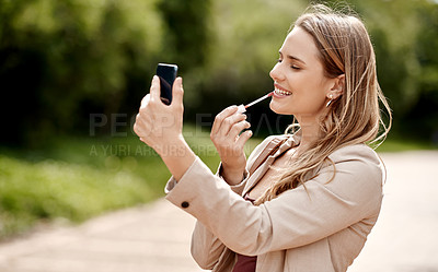Buy stock photo Shot of a young businesswoman applying lipstick using a smartphone against a city background