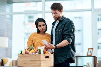 Buy stock photo Shot of a young couple going through their receipts at home after buying groceries