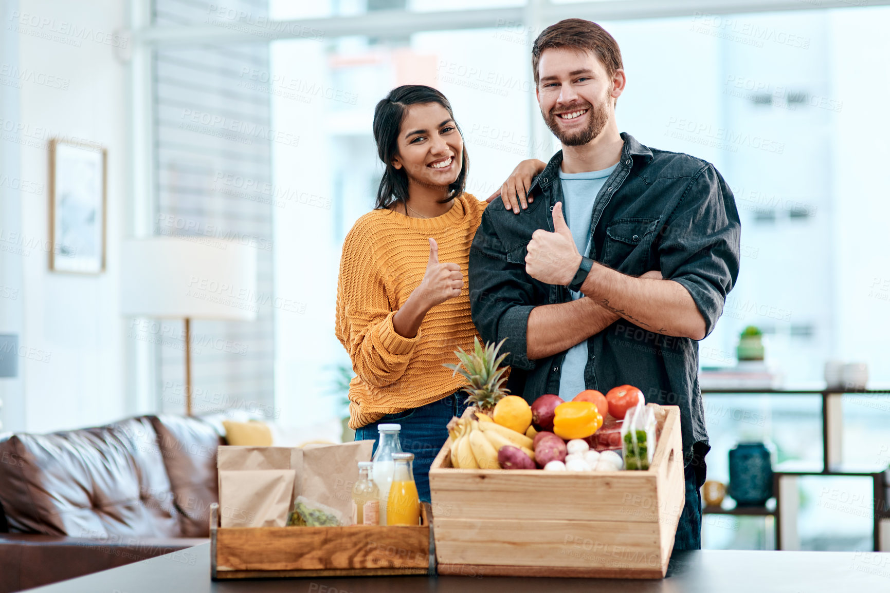 Buy stock photo Shot of a happy young couple showing thumbs up after unpacking their healthy groceries at home
