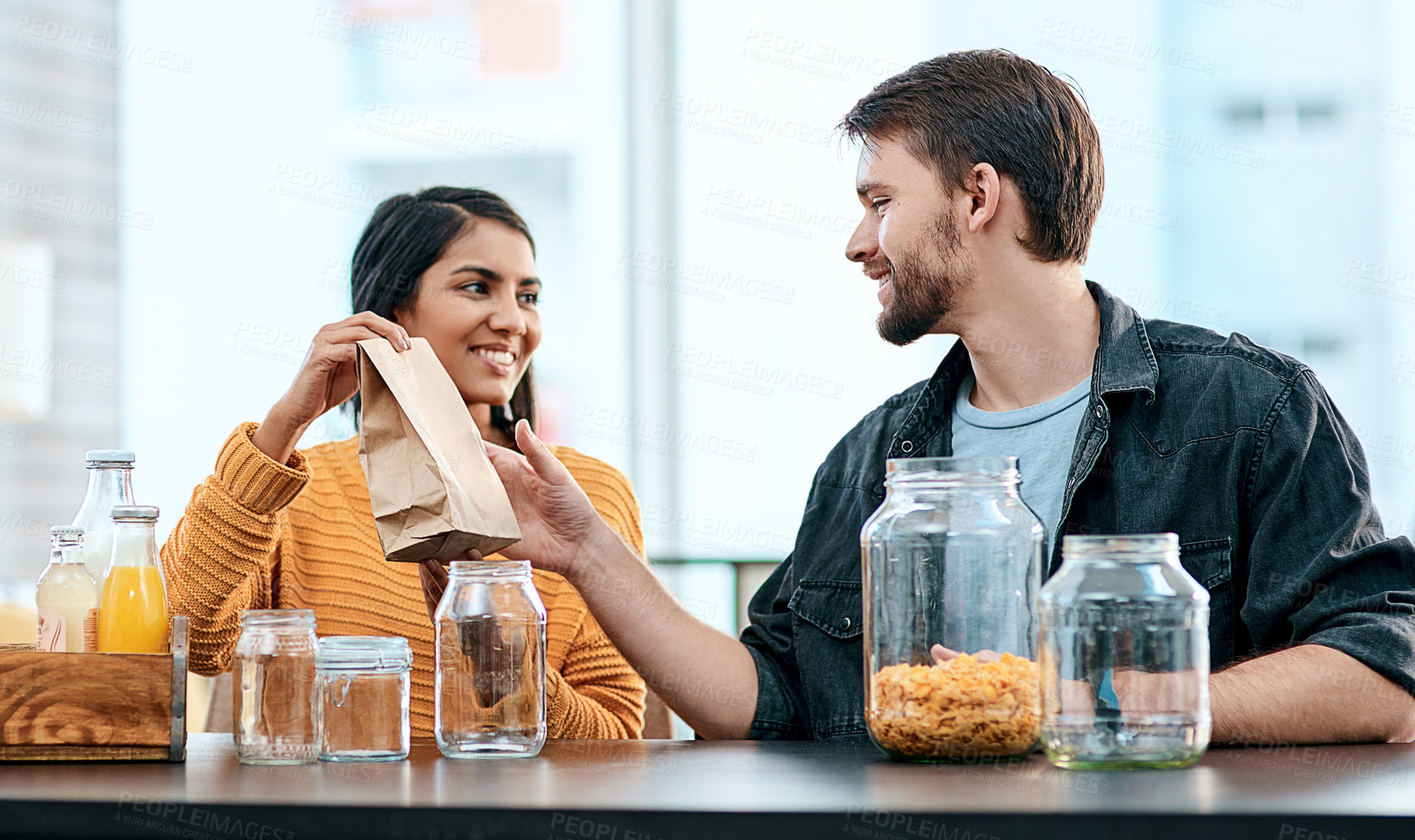 Buy stock photo Shot of a young couple packing their groceries into glass containers after returning home from the store