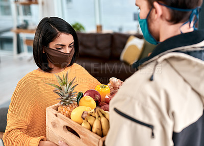Buy stock photo Shot of a masked young woman receiving a delivery of fresh fruit and vegetables at home