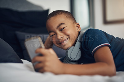Buy stock photo Shot of a young boy using a cellphone while lying on his bed