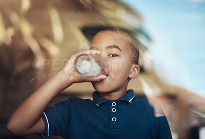 Buy stock photo Cropped shot of a young boy drinking a glass of water at home