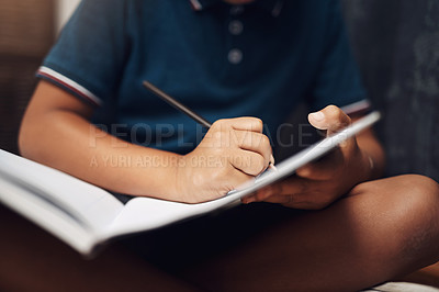 Buy stock photo Cropped shot of an unrecognizable boy writing in a book at home