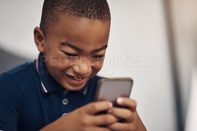 Buy stock photo Shot of a young boy using a cellphone while sitting on his bed