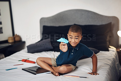 Buy stock photo Shot of a young boy making paper planes while sitting on his bed