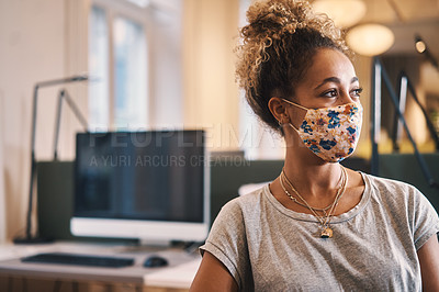 Buy stock photo Cropped shot of an attractive young businesswoman looking thoughtful while sitting in her office wearing a mask