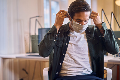 Buy stock photo Cropped shot of a handsome young businessman putting on his mask while sitting in the office
