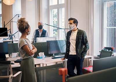 Buy stock photo Cropped shot of two young business colleagues having a discussion in their office while wearing masks