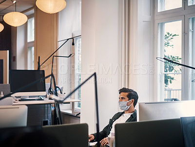 Buy stock photo Cropped shot of a handsome young businessman wearing a mask while working in the office
