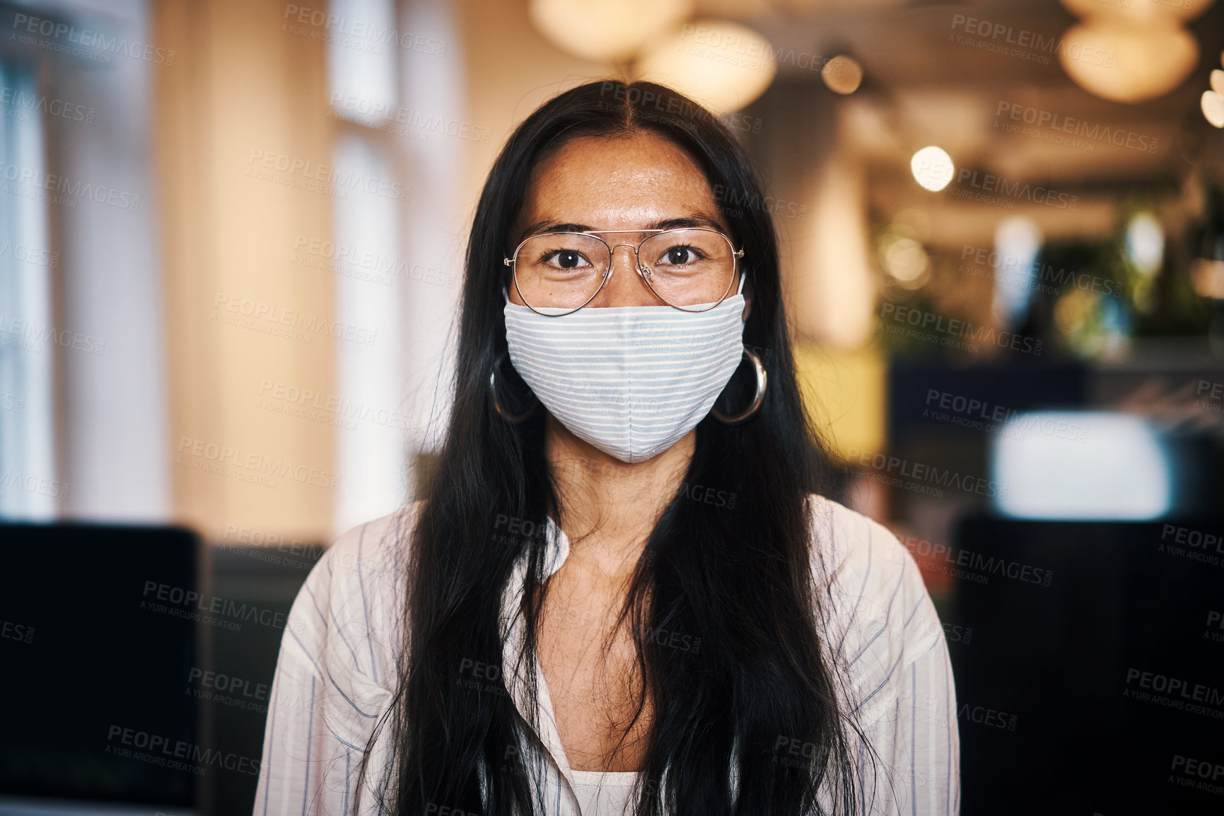 Buy stock photo Cropped portrait of an attractive young businesswoman standing in her office while wearing a mask